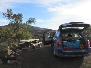 Car next to a picnic table in an old lava field